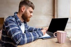 Junger Mann, der über Netzbuch während des Arbeitsbruches in der Kaffeestube, Mann sitzt in der offenen Laptop-Computer der Front Stockfoto