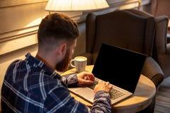 Junger Mann, der über Netzbuch während des Arbeitsbruches in der Kaffeestube, Mann sitzt in der offenen Laptop-Computer der Front Stockbilder
