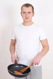 Junger Mann, der über Weiß kocht Stockbild