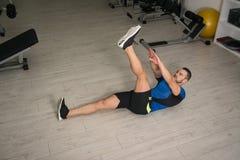 Junger Mann, der Abdominal- Übung auf Boden durchführt Lizenzfreies Stockfoto