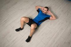 Junger Mann, der Abdominal- Übung auf Boden durchführt Stockbild