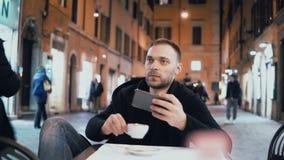 Junger Mann, der am Abend im Stadtcafé und im Holding Smartphone sitzt Attraktiver männlicher trinkender Kaffee allein stock video