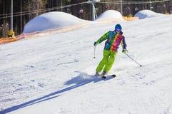 Junger Mann, der abwärts auf Winterurlaubsort Ski fährt stockfotografie