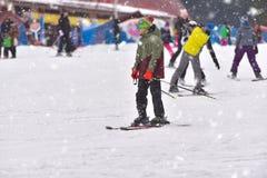Junger Mann, der abwärts mit Leuten im Hintergrund, schneebedecktes d Ski fährt Stockfotografie