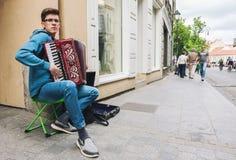 Junger Mann, der Akkordeon auf der Straße spielt Stockfotos