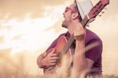 Junger Mann, der Akustikgitarre spielt und draußen singt Lizenzfreie Stockfotos