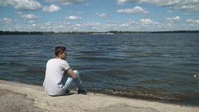 Junger Mann, der alleine sitzt stock video footage