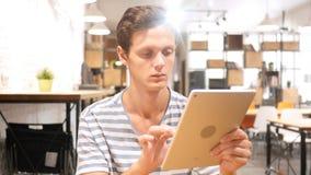 Junger Mann, der Anwendungen auf Tablet-Computer, Porträt verwendet stockfotografie