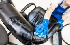 Junger Mann in der Arbeitskleidung und in den Gummihandschuhen säubert den Bürostuhl mit Berufsausrüstung stockfoto
