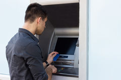 Junger Mann, der ATM verwendet stockbild