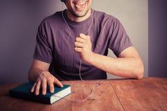 Junger Mann, der auf Audiobuch hört Stockfotos
