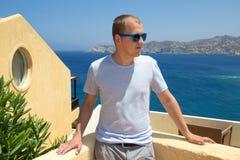 Junger Mann, der auf Balkon mit Seeansicht steht Lizenzfreies Stockbild
