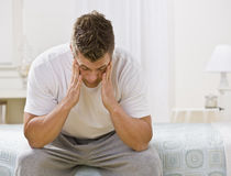 Junger Mann, der auf Bett sitzt lizenzfreies stockbild