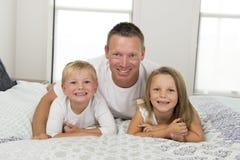 Junger Mann, der auf Bett zusammen mit ihren kleinen altes Sohn- und Tochterspielen des Bonbons 3 und 7 Jahren glücklich in Famil Stockbild