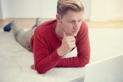 Junger Mann, der auf Boden liegt und Laptop betrachtet Lizenzfreies Stockbild