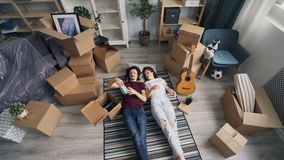 Junger Mann, der auf Boden mit Freundin zu Hause liegen während der Verlegung auspackt stock footage