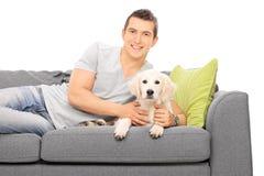 Junger Mann, der auf Couch mit einem Welpen liegt Stockfotografie