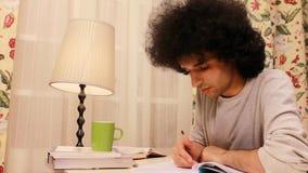 junger Mann, der auf das Buch 2 studiert und schreibt stock video footage