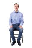 Junger Mann, der auf dem Bürostuhl lokalisiert auf Weiß sitzt Lizenzfreie Stockfotos