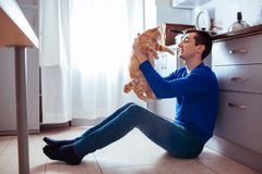Junger Mann, der auf dem Boden der Küche mit einer Katze sitzt lizenzfreies stockbild