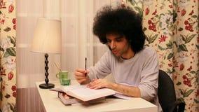 junger Mann, der auf dem Buch studiert stock footage