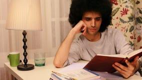 junger Mann, der auf dem Buch 2 studiert stock video