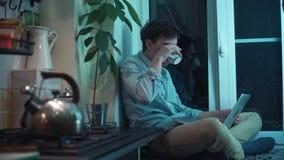 Junger Mann, der auf dem Computer sitzt an der Küche während Teekessel kocht auf Ofen schreibt stock video footage