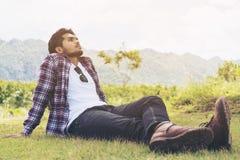Junger Mann, der auf dem Denken des grünen Grases sitzt Stockbilder