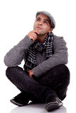 Junger Mann, der auf dem Fußboden, denkend sitzt Stockbilder