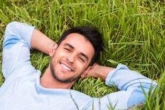 Junger Mann, der auf dem grünen träumenden Gras und die Kamera betrachten liegt relax lizenzfreies stockbild
