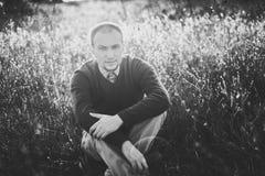 Junger Mann, der auf dem Gras bei Sonnenuntergang sitzt Stockbilder