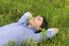 Junger Mann, der auf dem Gras liegt Lizenzfreie Stockfotografie