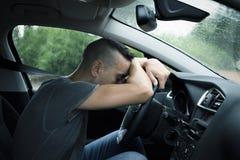 Junger Mann, der auf dem Lenkrad eines Autos stillsteht Lizenzfreies Stockbild