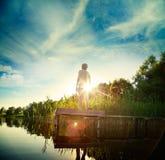 Junger Mann, der auf dem Pier durch See steht Stockbild