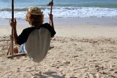 Junger Mann, der auf dem Schwingen auf dem Strand, fühlend sitzt, allein so traurig, einsam lizenzfreie stockbilder