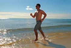 Junger Mann, der auf dem seachore läuft oder rüttelt lizenzfreie stockfotos