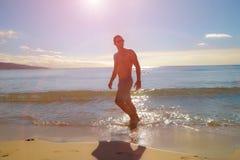 Junger Mann, der auf dem seachore läuft oder rüttelt stockbild