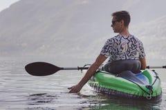 Junger Mann, der auf dem See Kayak f?hrt lizenzfreies stockbild