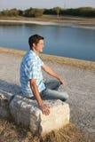 Junger Mann, der auf dem See sitzt Lizenzfreie Stockfotografie