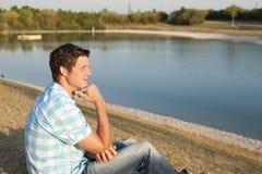 Junger Mann, der auf dem See sitzt Lizenzfreie Stockbilder