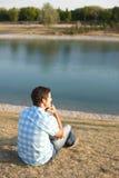 Junger Mann, der auf dem See sitzt Lizenzfreies Stockbild