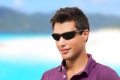 Junger Mann, der auf dem Strand lächelt Lizenzfreie Stockfotos