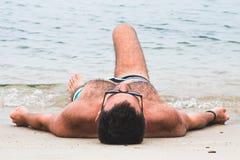 Junger Mann, der auf dem Strand liegt stockbilder