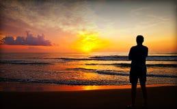 Junger Mann, der auf dem Strand sich entspannt Lizenzfreie Stockfotos