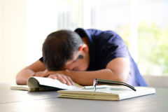 Junger Mann, der auf dem Tisch mit dem Buch geöffnet schläft Lizenzfreie Stockfotografie