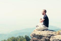 Junger Mann, der auf den Berg meditiert Stockbilder
