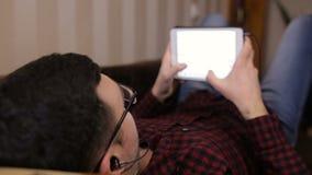 Junger Mann, der auf der sind Couch und der Gewinnung sms auf einer Tablette und dem Hören Musik liegt stock video