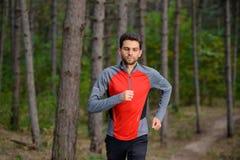 Junger Mann, der auf der Spur in der wilden Kiefer Forest Active Lifestyle läuft Lizenzfreie Stockfotografie