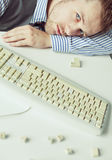 Junger Mann, der auf der Tabelle mit Tastatur liegt Lizenzfreies Stockfoto