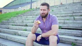 Junger Mann, der auf der Treppe isst einen Apfel, Schieberschuß, Recht sitzt stock video footage